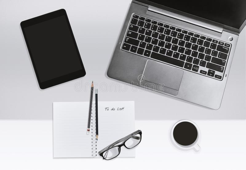 Modern office workplace concept. Laptop and notebook with task list and coffee cup. stock photo