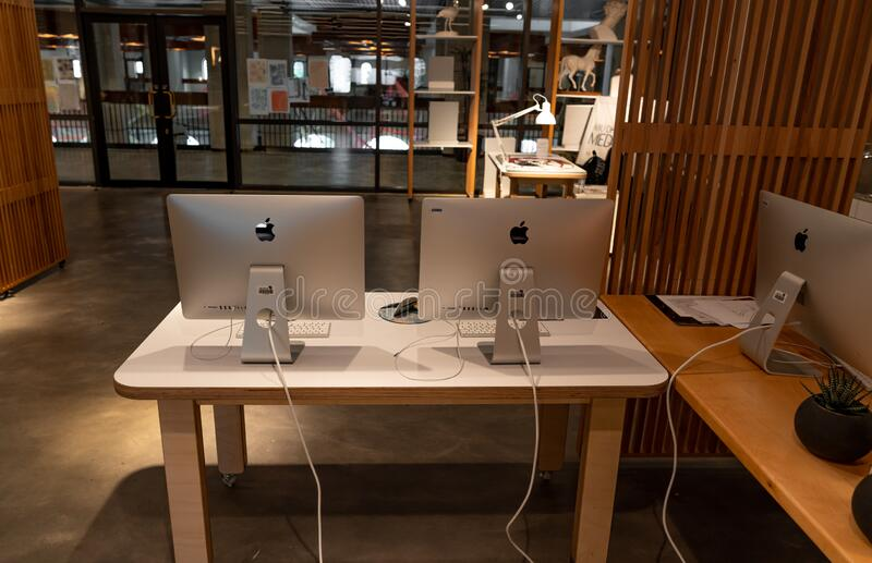 Modern office workspace station with apple iMac computers on a wooden white table - Creative space and work stock images