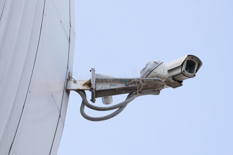 Modern old CCTV camera on a white wall or tiled building edge. Sky background. Concept of surveillance and monitoring. Modern old CCTV camera on a white wall or royalty free stock images