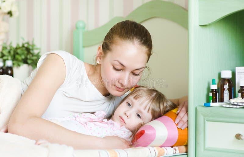 Modern omfamnar det sjuka barnet arkivbild