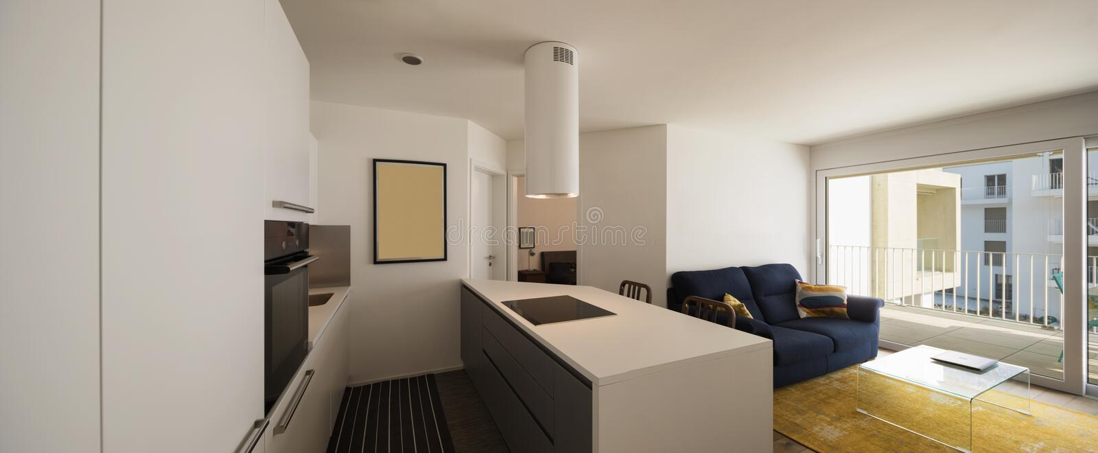 Elegant kitchen and living room in modern apartment stock photography