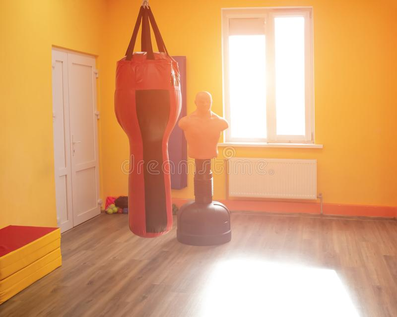 Modern orange boxing and karate room with sun on the window, gym, background, dummy stock photo
