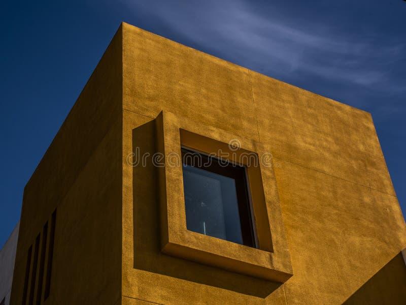 Modern orange byggnad mot en blå himmel arkivbilder