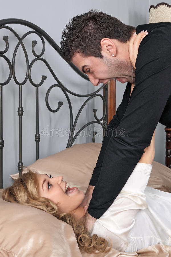 Modern Othello. The young man smothers the young girl on a bed stock photo