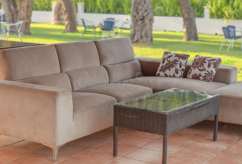 Modern outdoor cozy couch furniture in the garden on summer day. Terrace romantic house royalty free stock photo