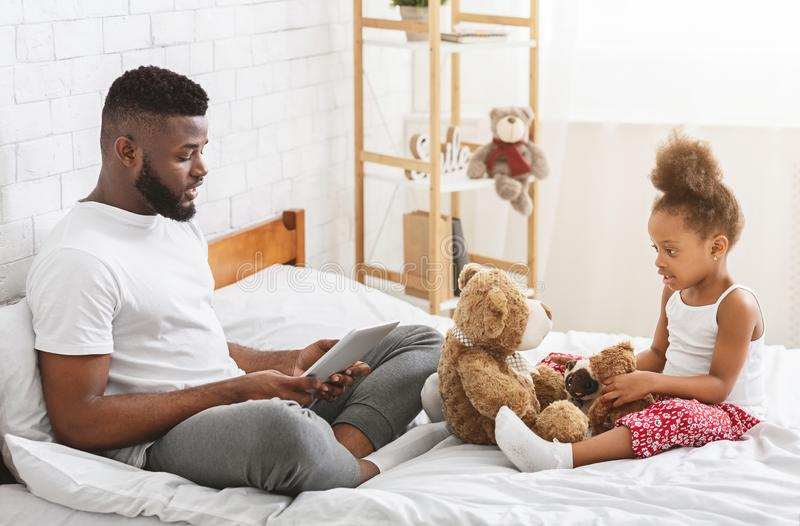 Busy african man browsing on tablet, sad little girl playing with toys alone stock photos