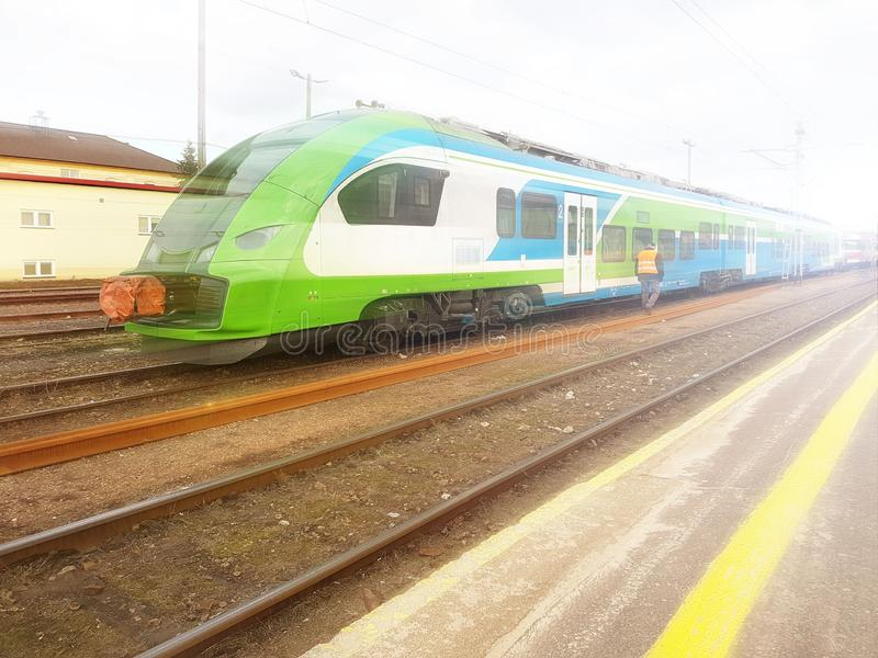 Modern passenger train en route. Worker inspects the railway line. High-speed train with motion blur. Train at the railway station. Schedule of arrival and stock images