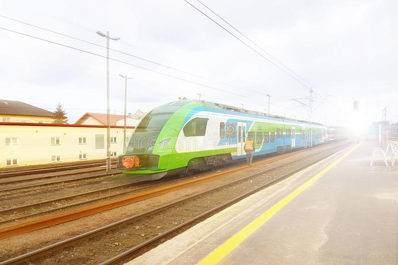 Modern passenger train en route. Worker inspects the railway line. High-speed train with motion blur. Train at the railway station. Schedule of arrival and royalty free stock photo
