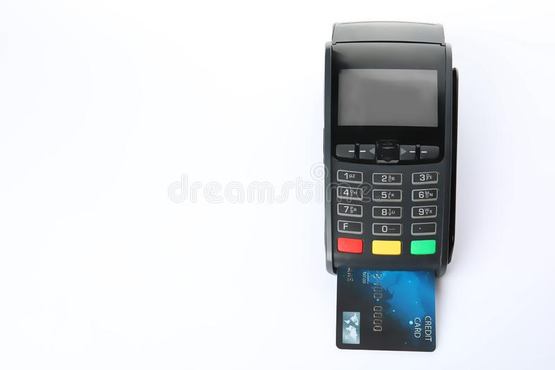 Modern payment terminal with credit card on white background. Top view stock image