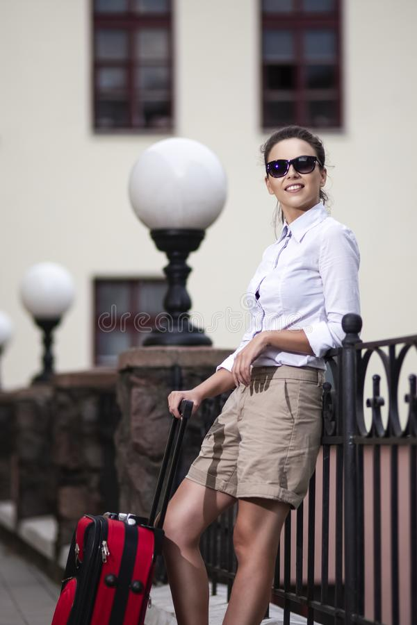 Modern People Traveling. Young Caucasian Woman in Sunglasses Posing With Roller Case During Her Travel Outdoors stock photography