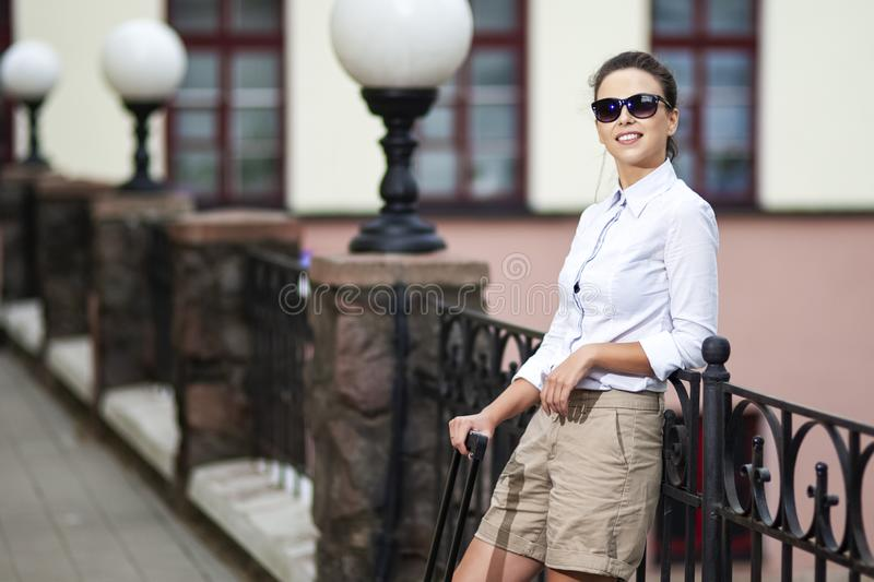 Modern People Traveling. Young Caucasian Woman in Sunglasses Posing With Roller Case During Her Travel Outdoors royalty free stock photos