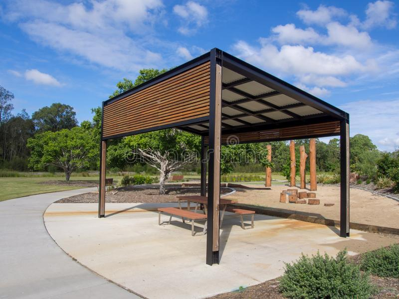 Modern pergola and sitting area with play ground behind in Public Park. On a sunny day stock photography
