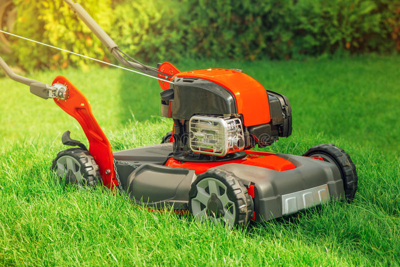 Modern petrol powered rotary push grass lawn mower. In house backyard royalty free stock images