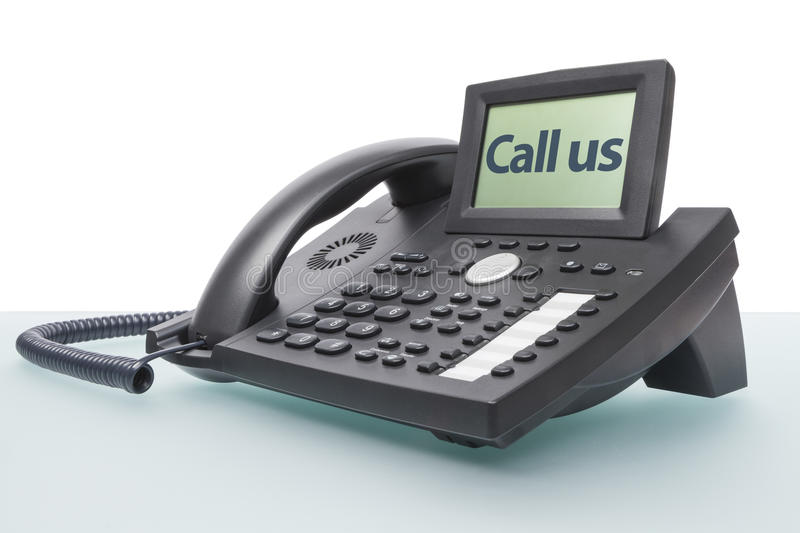 Modern phone on glass desk. Modern business voip phone on glass desk with the words - Call us - in the display royalty free stock photography
