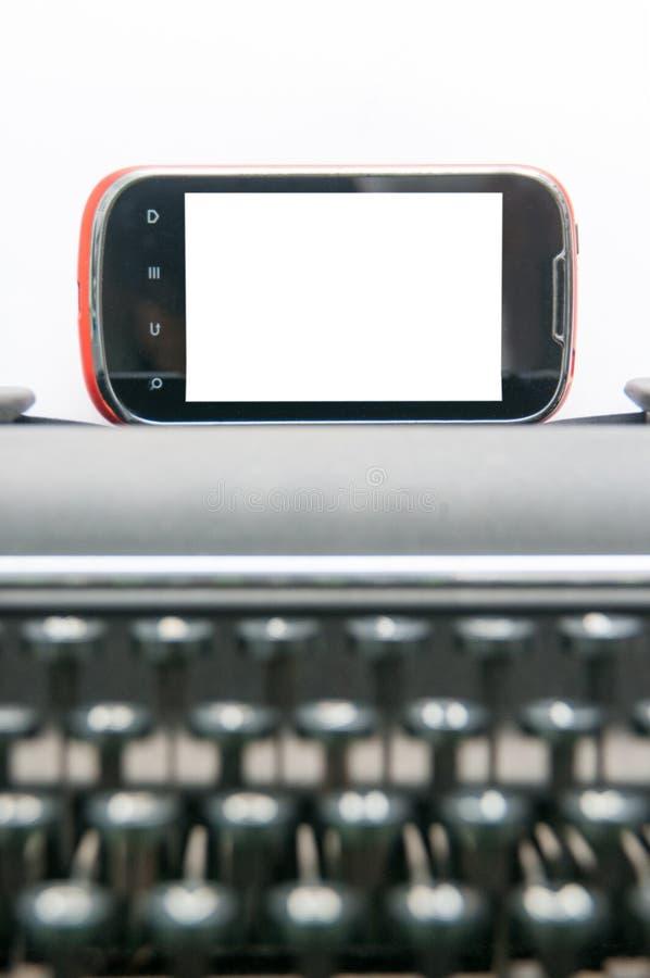 Modern phone and vintage typewriter royalty free stock photo
