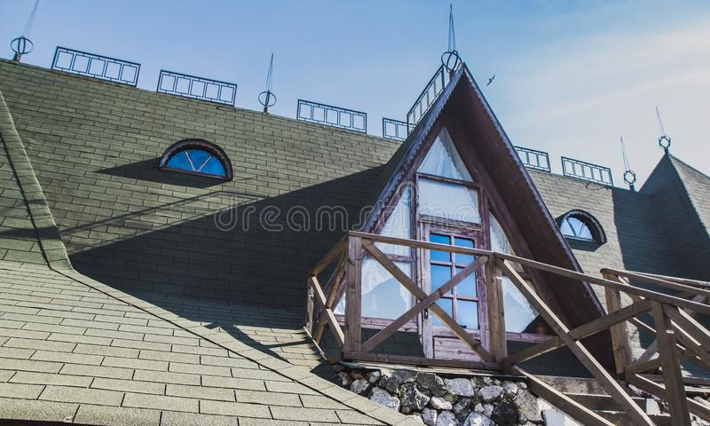 Modern photo of a rural rustic facade  balcony of a stylish cottage . Window of mansard of the wooden house against the summer blu. E sky - natural lifestyle royalty free stock image