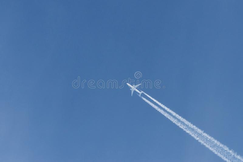Modern plane flying high in the blue sky at sunny day. Speed and energy.  stock photography