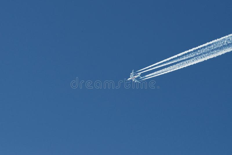 Modern plane flying high in the blue sky at sunny day. Speed and energy.  royalty free stock photography