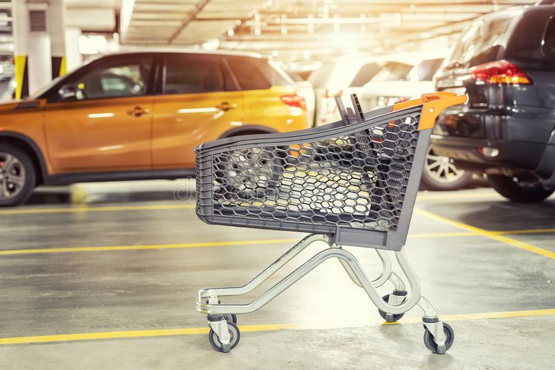Modern plastic empty shopping cart left at roofed underground parking of shopping mall. Supermarket trolley with blurred parked stock image
