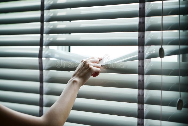 Modern plastic shutter blinds with hand royalty free stock images