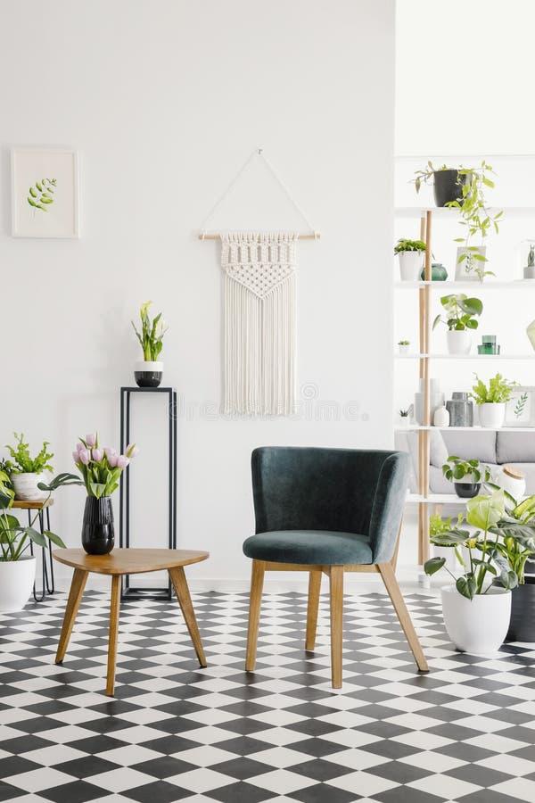 Modern plats och retro kaffetabell på ett rutigt golv i en botanisk vardagsruminre Verkligt foto royaltyfria bilder