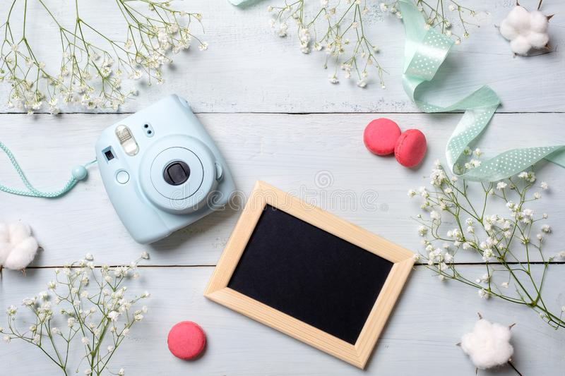 Modern polaroid camera, macaroon cookies, photo frame, flowers on rustic blue wooden background. Top view, tender minimal flat lay stock photos