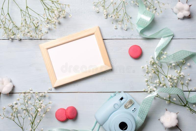 Modern polaroid kamera, makronkakor, fotoram, blommor på lantlig blå träbakgrund Den bästa sikten, den mjuka minsta lägenheten lä arkivbilder