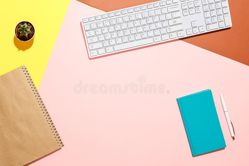 Modern positive workspace. Flat lay composition of keyboard, cactus, diary with pen on colorful desk. Pink, yellow royalty free stock images