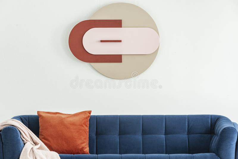 Modern poster on white wall above blue sofa with orange cushion and pink blanket in interior. Real photo stock photography