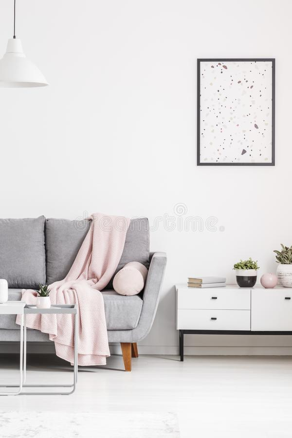 Modern poster on a white wall, grey sofa with blanket and cabinet in a living room interior. Real photo. Concept royalty free stock photo