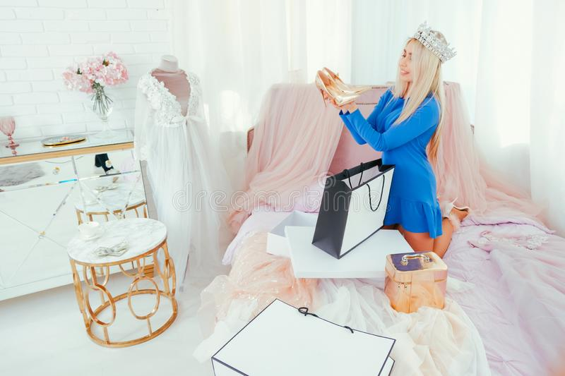 Modern princess lifestyle rich lady new shoes. Modern princess lifestyle. Rich lady in tiara holding new golden shoes. Sophisticated room interior stock images