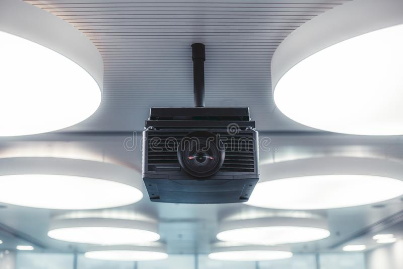A modern projector in a lecture room. A black modern projector with a plastic case and a huge lens with aberrations in it mounted to a striped ceiling with royalty free stock images
