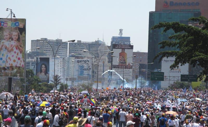 Modern protesterar allra i Venezuela Den Militar polisen började att avfyra tårgas på personer som protesterar arkivbild