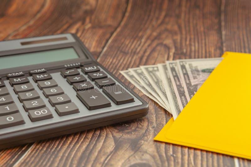 Modern r?knemaskin p? en tr?tabell med ett gula kuvert och pengar p? en suddig bakgrund, aff?rsid?, n?rbild arkivbild