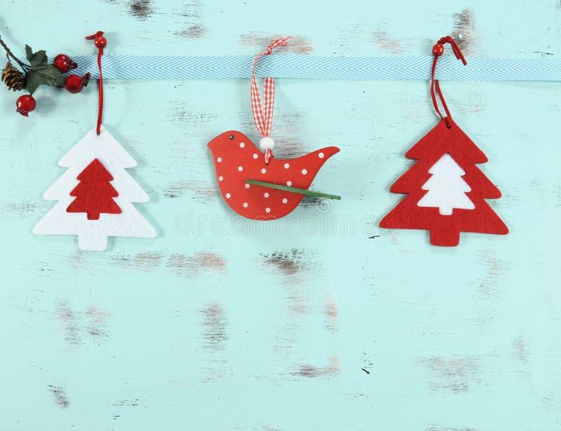 Modern röd och vit jul som hänger fågel- och trädgarneringar på aqua, slösar wood bakgrund fotografering för bildbyråer