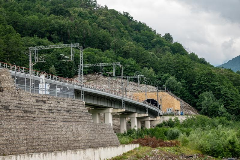 A modern railway bridge leads to a tunnel in the mountain. Railway in the mountains royalty free stock photography