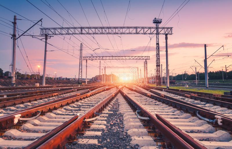 Modern railway station at night in Europe. Industrial landscape. With railroad junction, colorful sky at sunset. Railway platform in twilight. Railway royalty free stock image