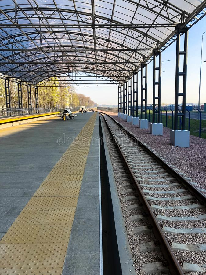 Modern railway station, train station with a transparent canopy for passengers and rails.  royalty free stock photo