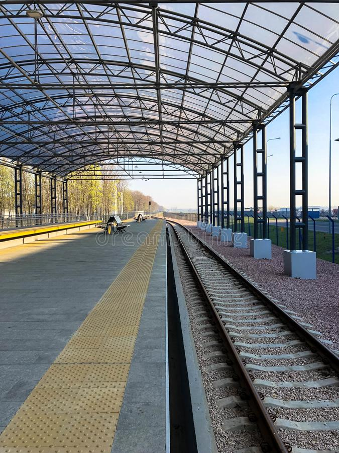 Modern railway station, train station with a transparent canopy for passengers and rails.  royalty free stock photography
