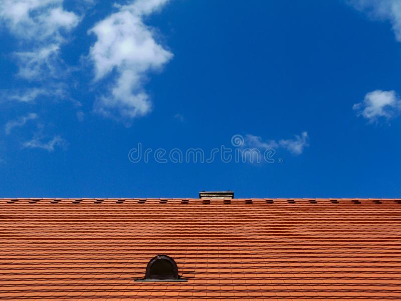 Modern red brown sloped clay roof with vent under blue sky. Modern red brown sloped clay roof with dormer type vent and metal flashing under blue sky with bright stock images