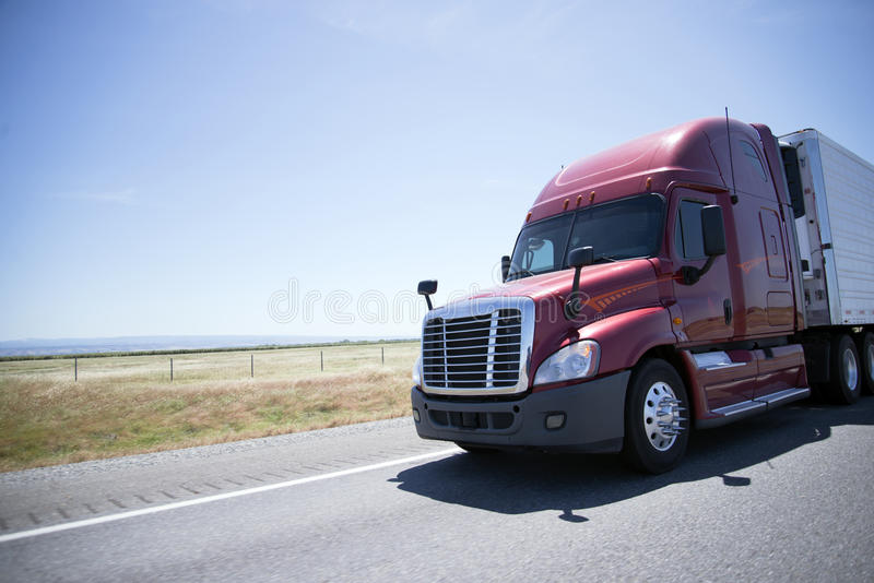 Modern red semi truck and reefer trailer on road in sunny day. A large, powerful modern semi truck with a reefer unit and refrigerated trailer carries perishable stock images