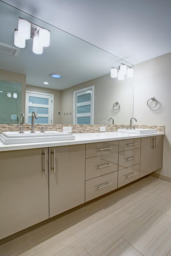 Modern refreshing bathroom with a beige dual washstand. Modern refreshing bathroom features a beige dual washstand accented with mosaic backsplash beneath a stock images
