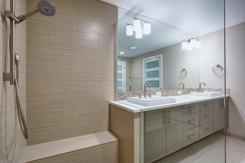 Modern refreshing bathroom with a walk-in shower. Modern refreshing bathroom features a Walk-in shower with beige subway tiled interior next to a dual washstand royalty free stock photos