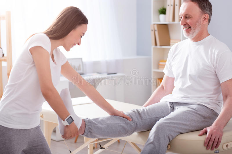 Modern rehabilitation physiotherapy. Eldercare. Smiling and positive young female physiotherapist stretching her male patient leg in a medical office royalty free stock photo