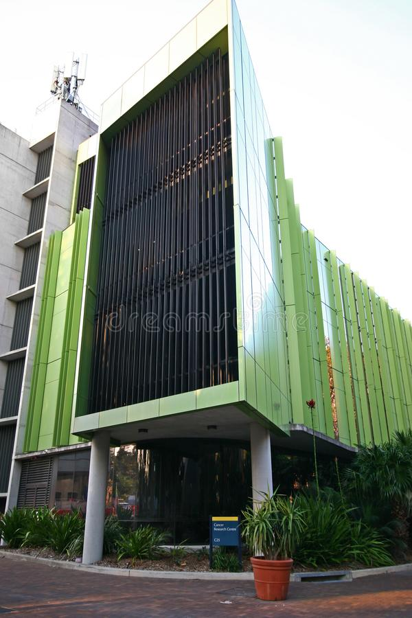 Lowy Cancer Research Centre with green metal panels and vertical slat screening on exterior facade at UNSW, Sydney, Australia. Modern research center with dark stock photography