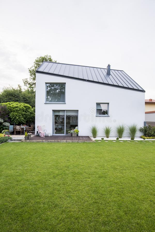 Modern residential house with white walls and black roof, garden. Furniture on a wooden terrace and beautiful, big lawn outside stock photography