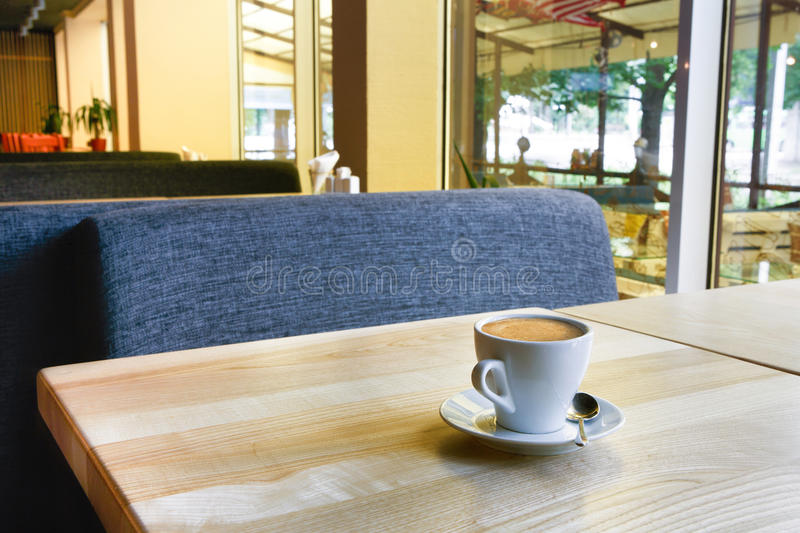 Modern restaurant, bar or cafe interior, coffee cup on table. Morning coffee in cafe. Espresso cup on table, empty restaurant or coffee shop interior royalty free stock image