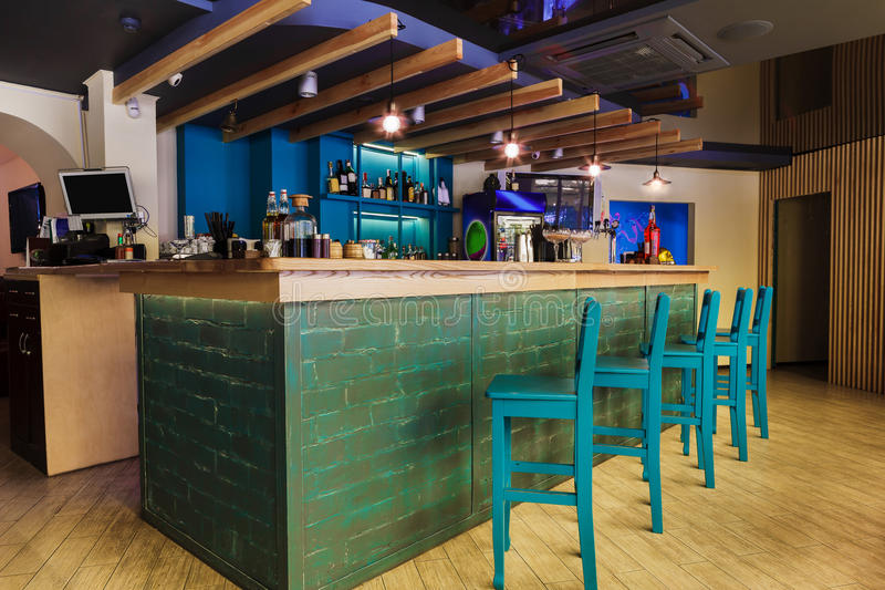 Modern restaurant, bar or cafe interior. Modern restaurant or cafe interior. Public place interior design, bright blue wooden chairs, large bar counter desk royalty free stock photos