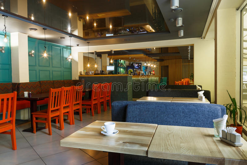 Modern restaurant, bar or cafe interior. Modern restaurant or cafe interior. Public place interior design, bright red wooden chairs and blue sofas, large windows stock photography