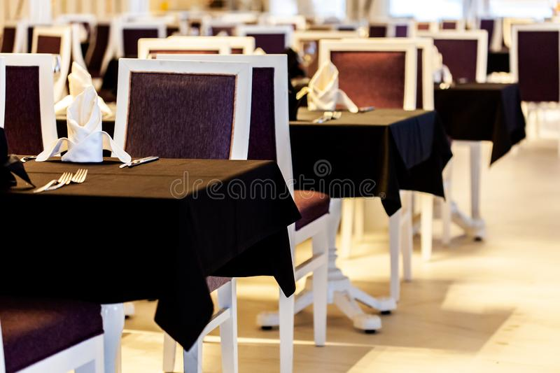 Modern restaurant or cafe in black and white colors. Table with black tablecloth close-up royalty free stock photo